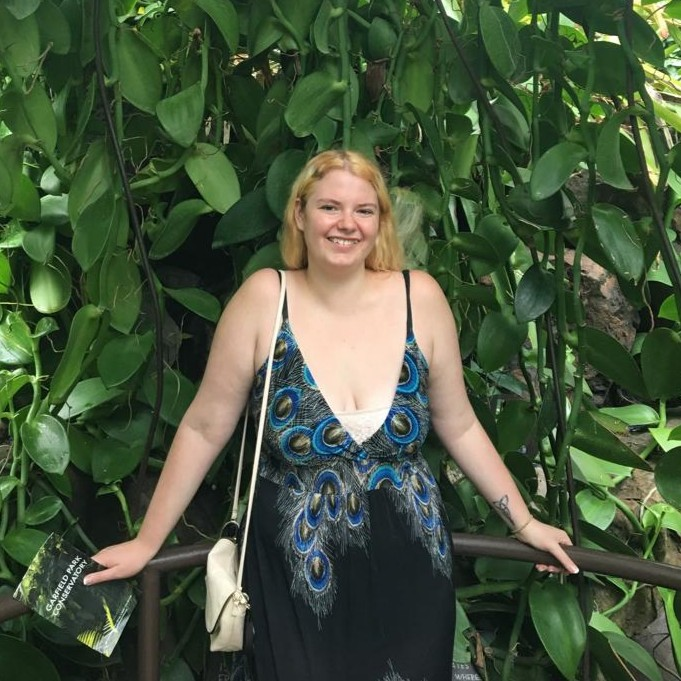 woman standing and smiling in front of leafy plants
