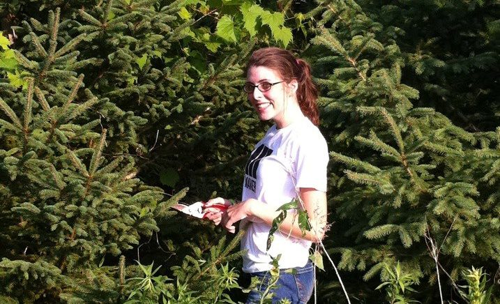 Hallie smiling holding shears in a grove of pine trees and mustang grape